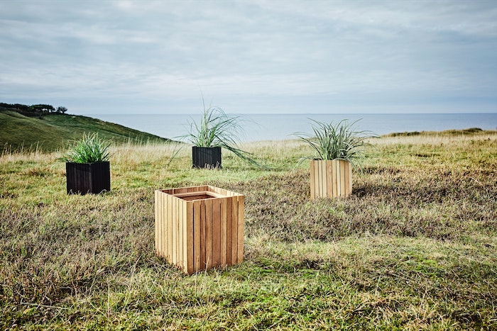 large wood planters in field overlooking water that might use filler in the bottom to make them heavy