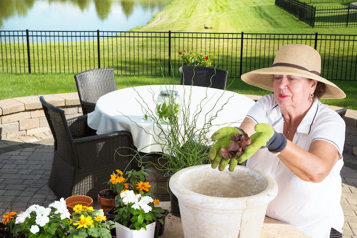 senior woman putting rocks to fill bottom of a large planter