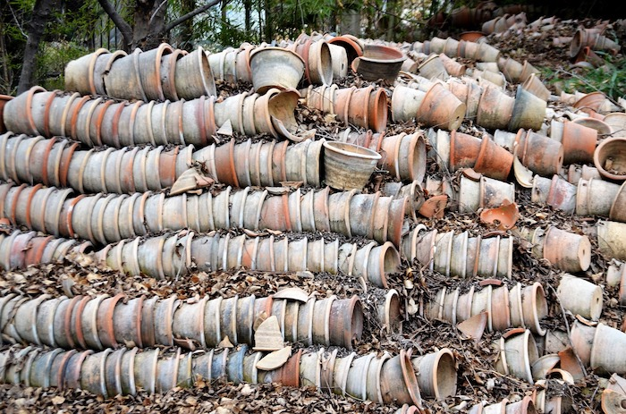 broken and unbroken clay pots lying in rows on their sides perfect for using as filler in the bottom of a large planter
